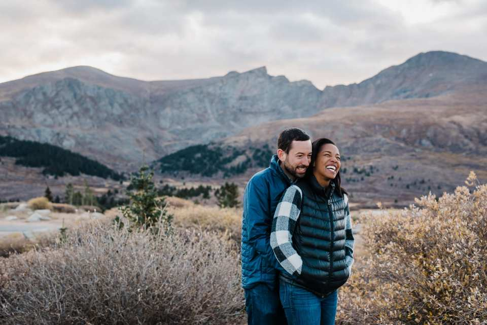 Couple snuggles by Colorado mountainside
