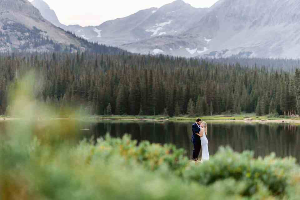 Couple kisses among the rocky mountains at Brainard Lake in Colorado. Brainard lake is one of the best spots near Denver for Engagement Photos.