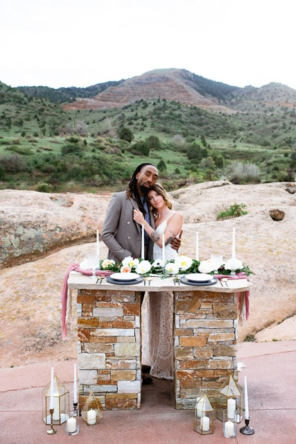 Red Rocks wedding inspiration to help you decide what type of ceremony is best for you and your partner. In an elopement vs wedding what is right for you? Here a couple hugs each other behind their sweetheart table at their Red Rocks, Colorado wedding.