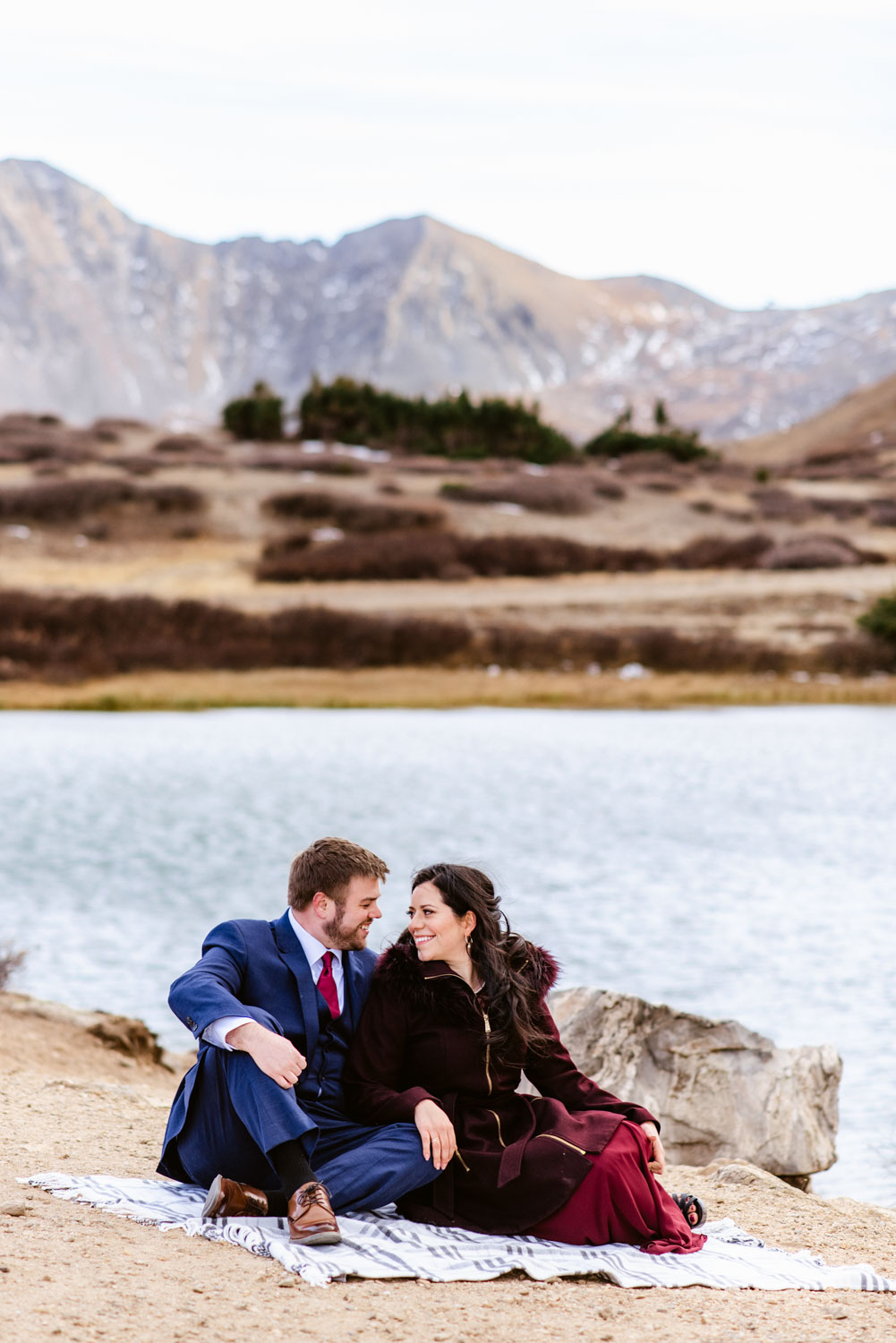 Couple snuggles on a blanket by Pass Lake on Loveland Pass in Colorado.