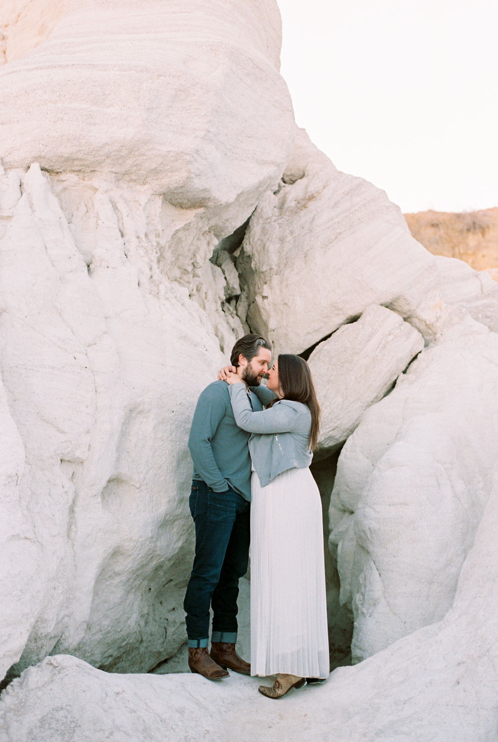 Engaged couple embraces in the landscape of Colorado's Paint Mines, one of the best locations for engagement photos near Denver.