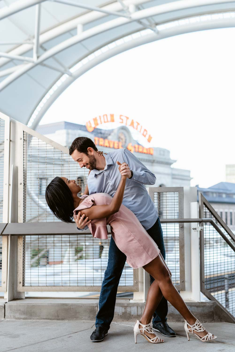 Newly engaged couple dips in front of the Union Station sign at Denver's Union Station downtown. Union Station is one of the best spots in Denver to take photographs because of its cool architecture and unique downtown.