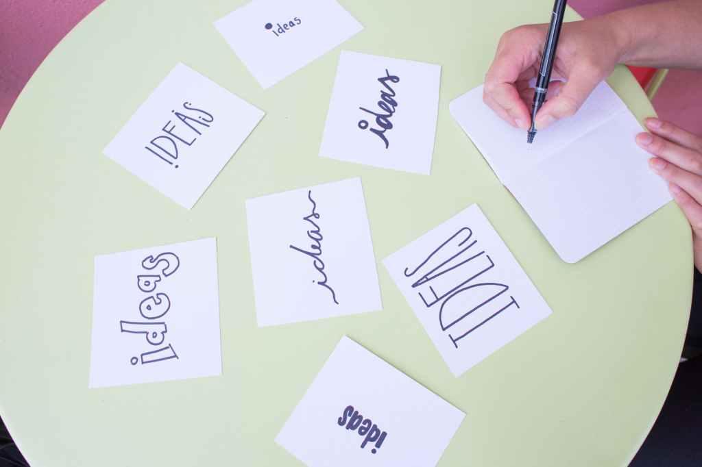 """Uma pessoa escreve num caderno sobre a mesa, em frente à folhas com a palavra """"ideas"""" em várias fontes."""