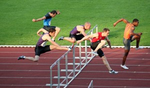 Men leaping over hurdles