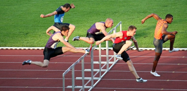 Men leaping over hurdles