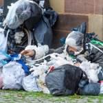 Armut In einer der reichsten Städte Deutschlands sitzt ein Obdachloser und hat seine ganzen Besitztümer um sich herum in