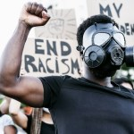 Activist,Wearing,Gas,Mask,Protesting,Against,Racism,And,Fighting,For