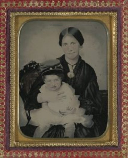 Unidentified woman, in mourning dress and brooch showing a Confederate soldier, holding a young boy wearing a kepi. Courtesy of the Library of Congress.