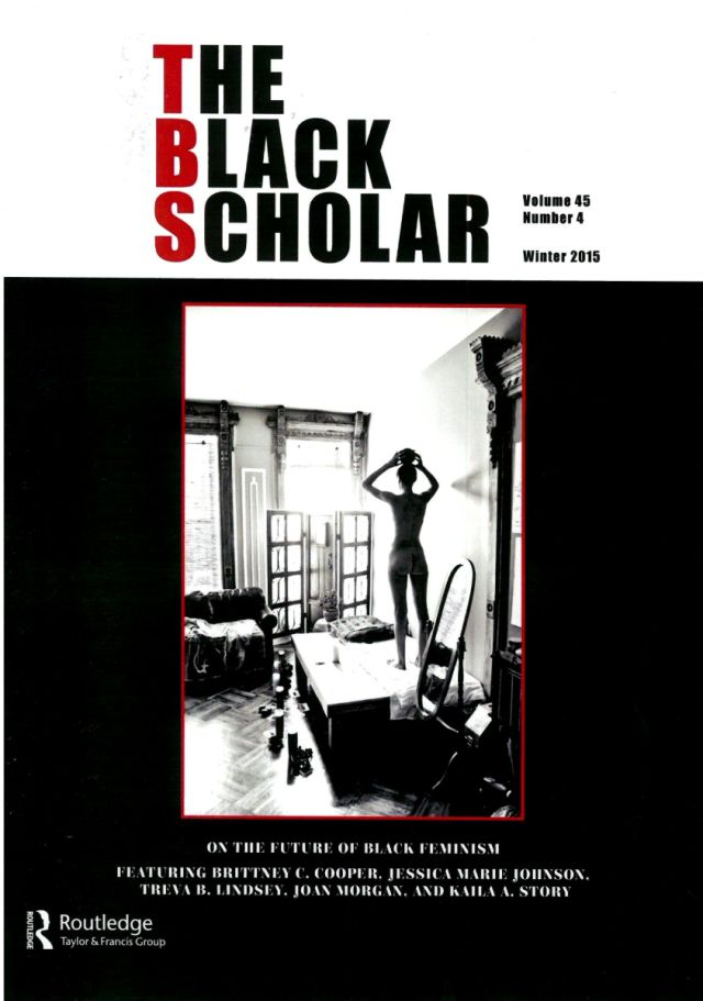 The Black Scholar, black and white picture of an apartment where a person is standing on a tablel.