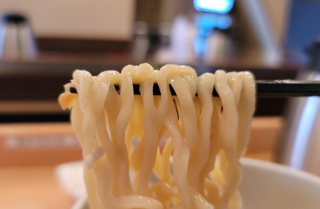 高田馬場のラーメン屋「蔭山」の鶏白湯塩そばの麺を割り箸で口に運ぶ