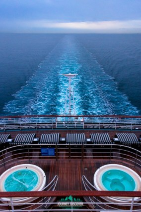 The back of a cruise ship as taken from aboard the boat with two jacuzzi spas and the wake and wash trailing behind