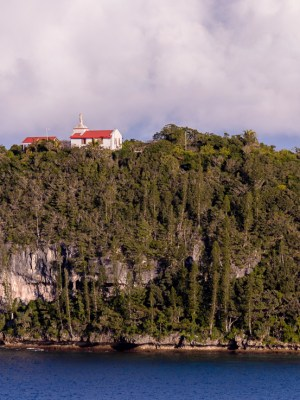 View of pacific island headland cliffs with church perched on top.