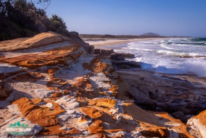 Northward views of Mt Coolum from Bare Rock, Sunshine Coast, Queensland, Australia  Orange and white rocky outcrop at the end of a beach with mountain in background