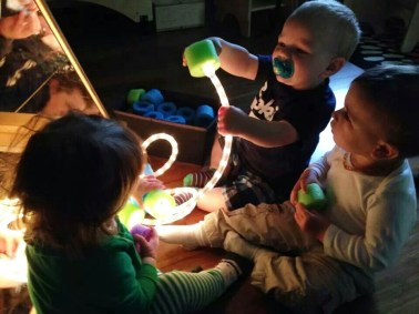 infants with light exploring materials