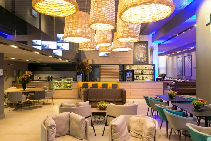 Hotel lobby of Novotel Curitiba Batel, with chandeliers, bar and comfy sofa seating