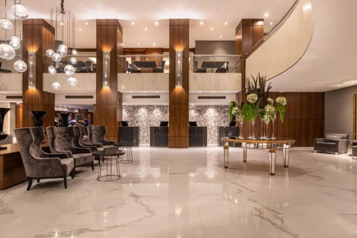 Modern lobby of Grand Hotel Rayon in Curitiba, with marble floor and structural light fixtures