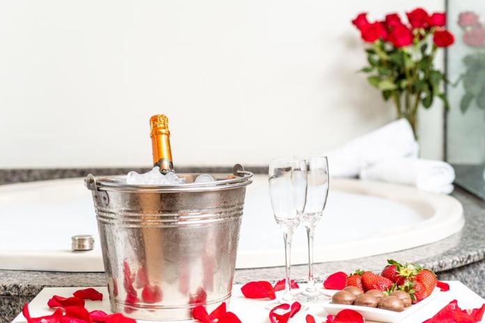 Spa bath with champagne bucket and roses at Rede Andrade Vernon in Curitiba