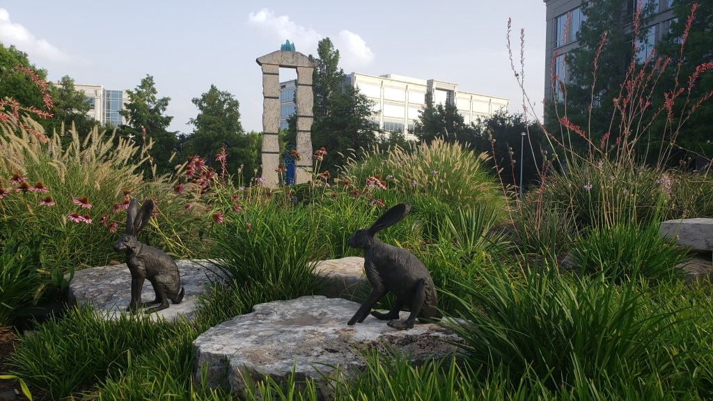 bronze rabbits over rocks with a tall two pillared stone temple sculpture in the background, surrounded by plants and flowers