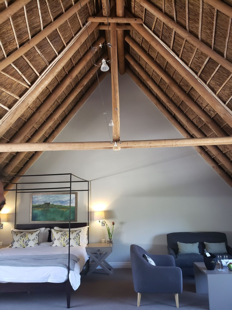 vaulted thatch roof with bed and sitting area underneath