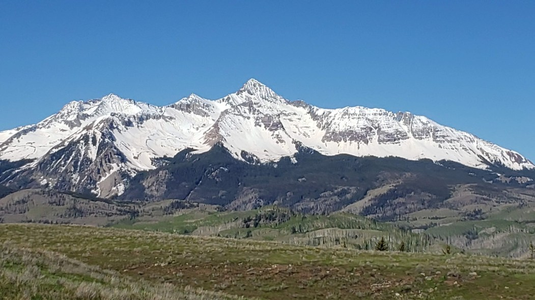 white snow capped mountains against a blue sky and open vistas