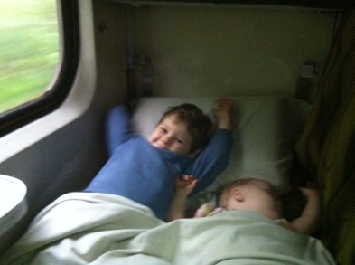 Sleeping on a train, despite her brother.
