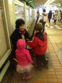 "Busker with ""Japanese Guitar"" at Oji station, Tokyo."