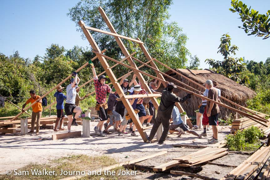 Volunteers erect the house frame of Volunteer Building Cambodia's 100th house