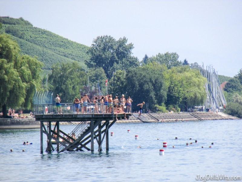 Kids having fun, jumping in Lake Constance near Meersburg