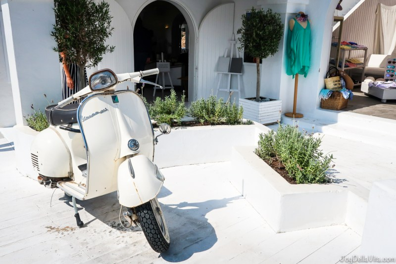 a white vintage Vespa at the entrance to Cotton Beach Club Ibiza