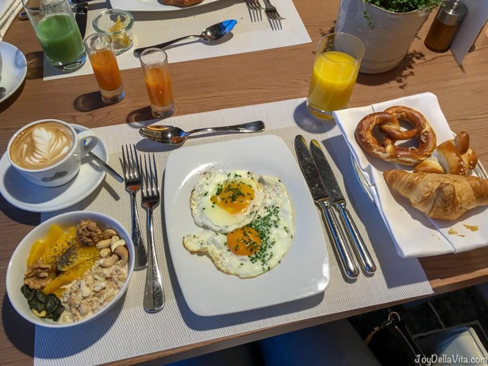 My Kempinski Berchtesgaden Breakfast with fried eggs, juice, cappuccino and fresh orange slices with bircher muesli