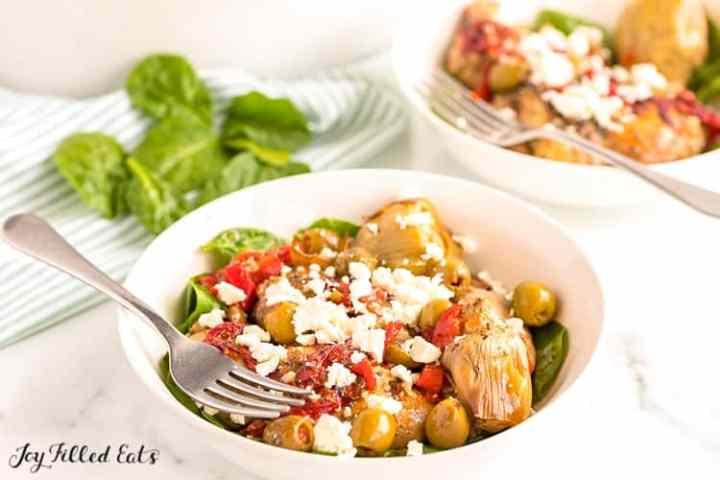 2 white bowls of mediterranean chicken with fresh spinach