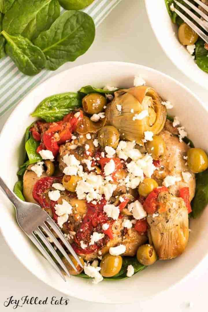 bowl of mediterranean chicken with fresh spinach