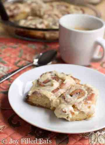 Two cinnamon rolls on a white plate on top of a floral placemat with a coffee cup and spoon