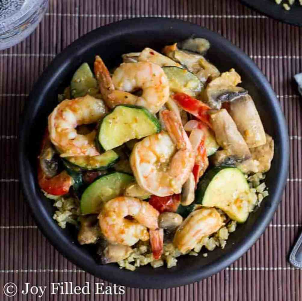 Cooked shrimp and vegetables in a black bowl on a bamboo placemat
