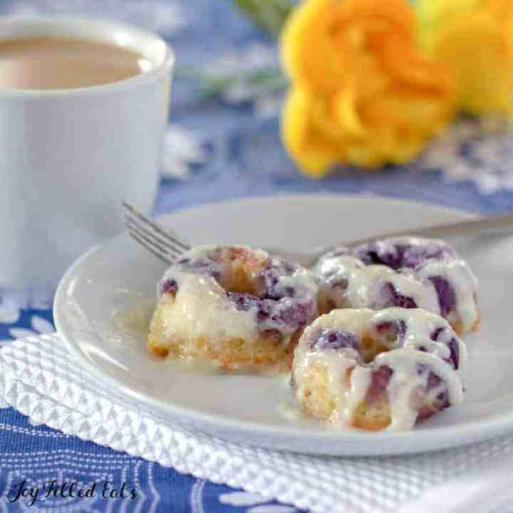 cream cheese glaze on lemon blueberry donuts on a white plate with a fork. coffee and flowers in background.