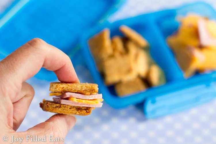 A hand holding a little sandwich made with meat cheese and cheese crackers