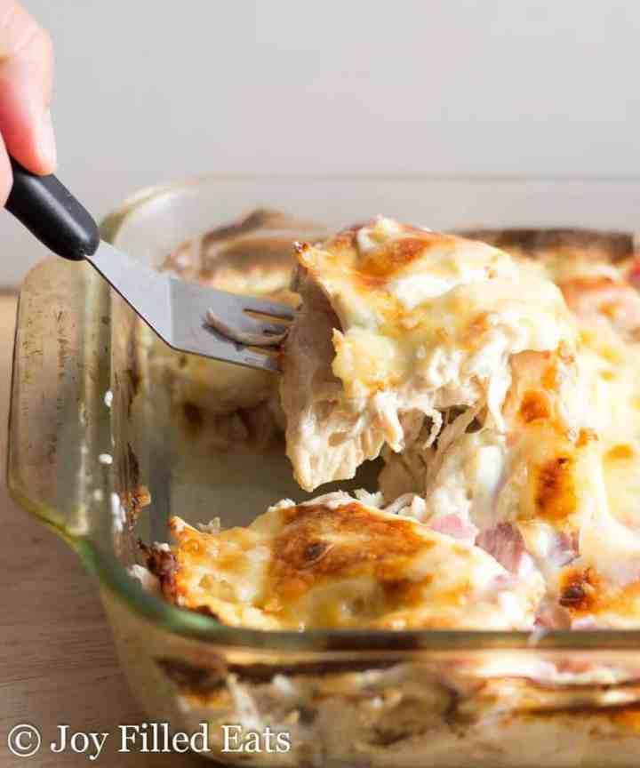 a hand lifting a spatula of chicken cordon bleu casserole