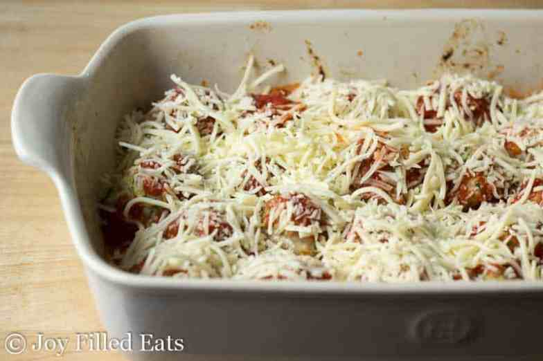 baked meatballs covered with sauce and cheese in a casserole dish