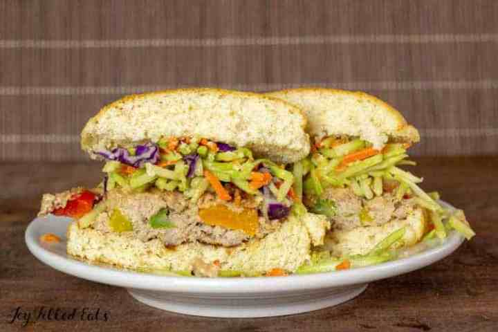 an asian burger cut in half showing the broccoli slaw topping on a bun