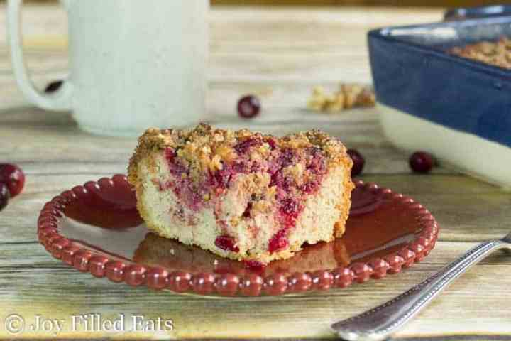 A slice of cranberry cake with walnut crumb topping on a red beaded plate
