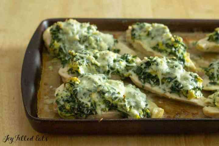 close up of spinach and cheese topped chicken on a stoneware baking pan