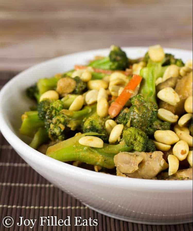 Thai Peanut Chicken in a large white bowl topped with peanuts