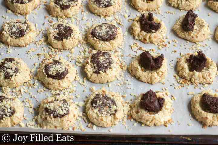 Almond Crunch Chocolate Thumbprint Cookies on a parchment lined cookie sheet