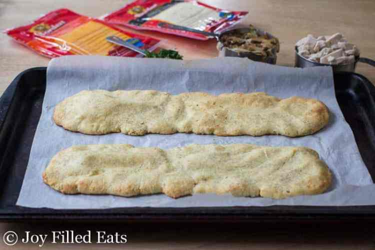 Two baked low carb flatbread on a parchment lined baking sheet