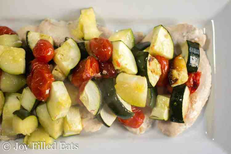 greek chicken topped with cooked vegetables
