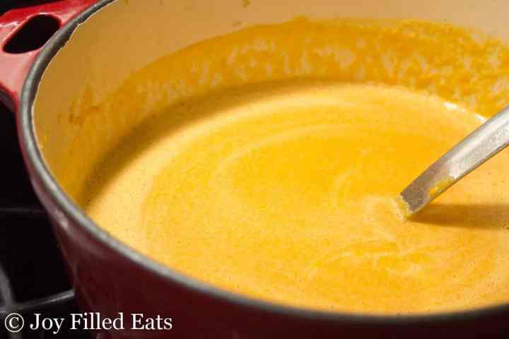 large soup pot with roasted red pepper soup and a ladle