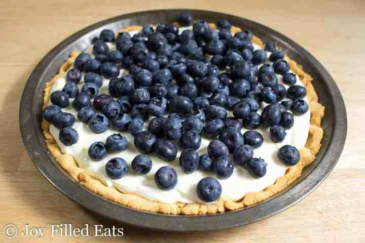 Lemon Ricotta Pie topped with blueberries in a tin pie plate