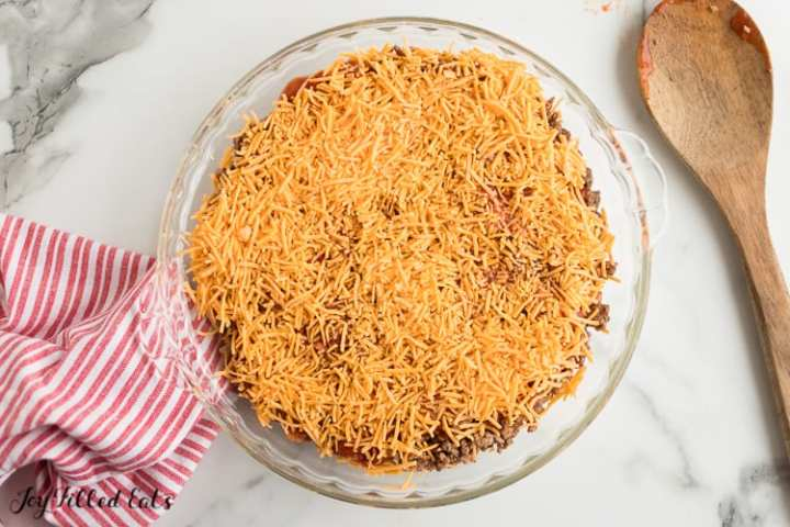 cheddar cheese on top of the layered taco dip