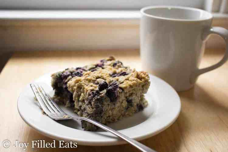Close up of Healthy Baked Oatmeal on a white plate with a fork. cup of coffee in the background
