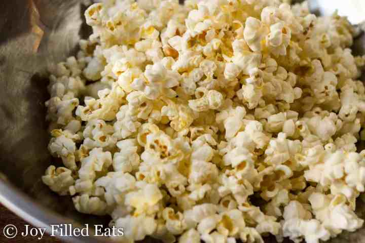 Close up of air popped popcorn in a stainless steel bowl.